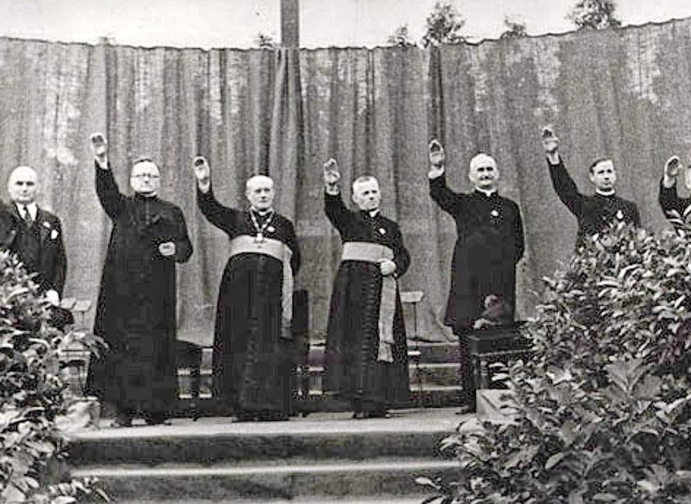 На этом фото Алоис Худал(второй слева) зигует вместе с другими священниками-нацистами.